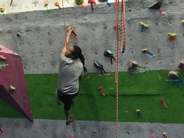 A CAN Lab Member climbing a rock wall