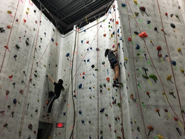 Two CAN Lab members climb a rock wall